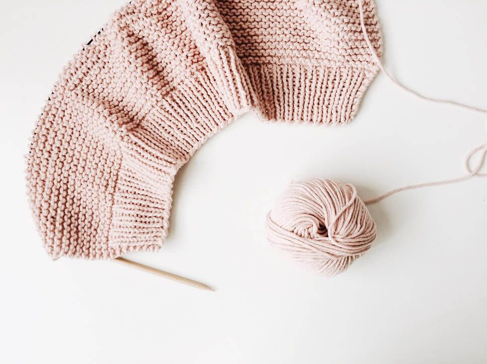 pink knitted hat with hand knitting needles