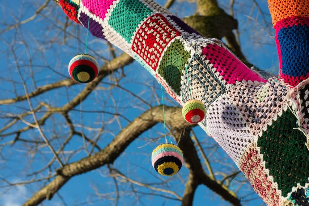 yarn bombing on a tree with blue sky